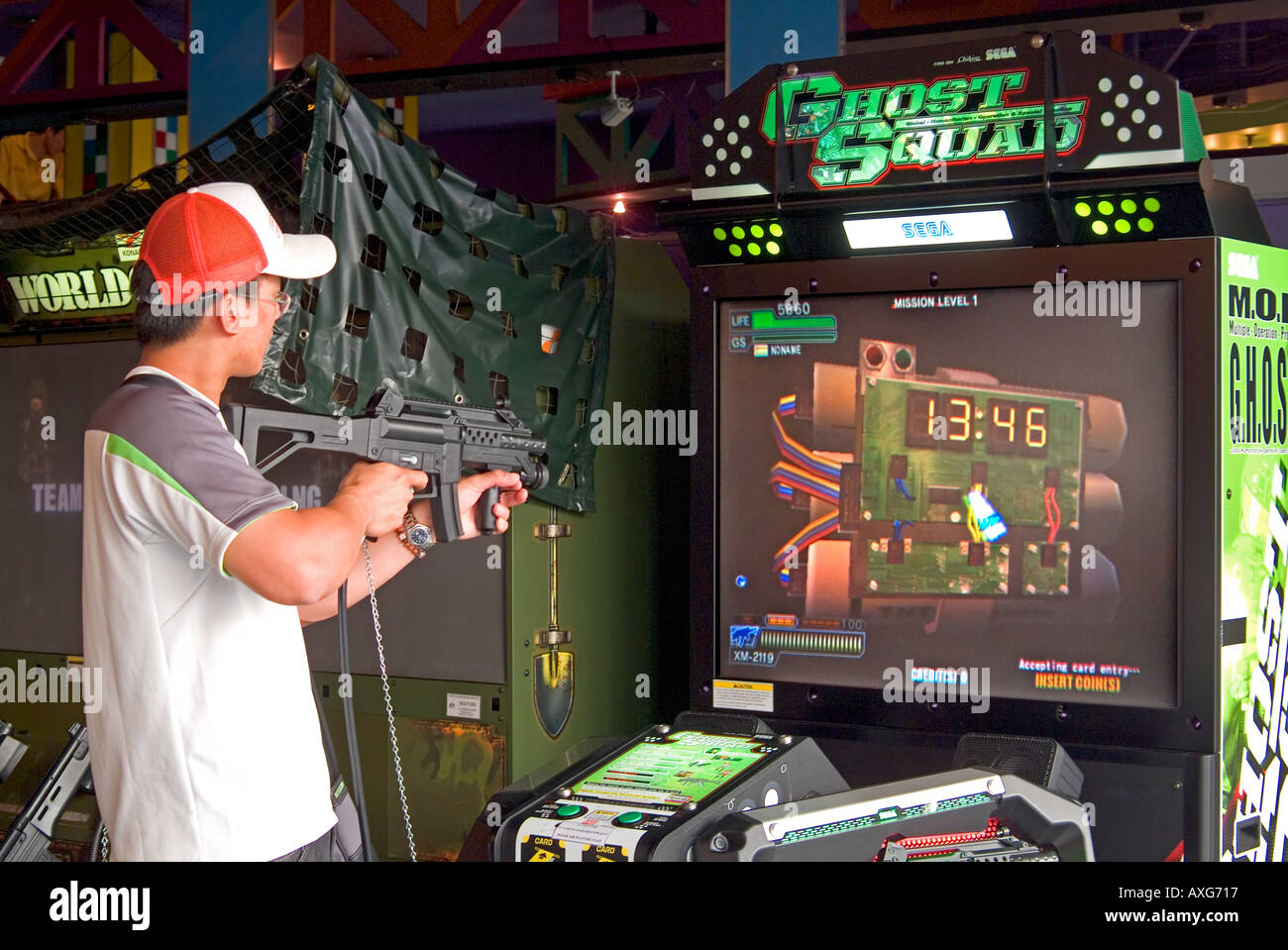 A young man playing a shooting arcade game - Stock Image
