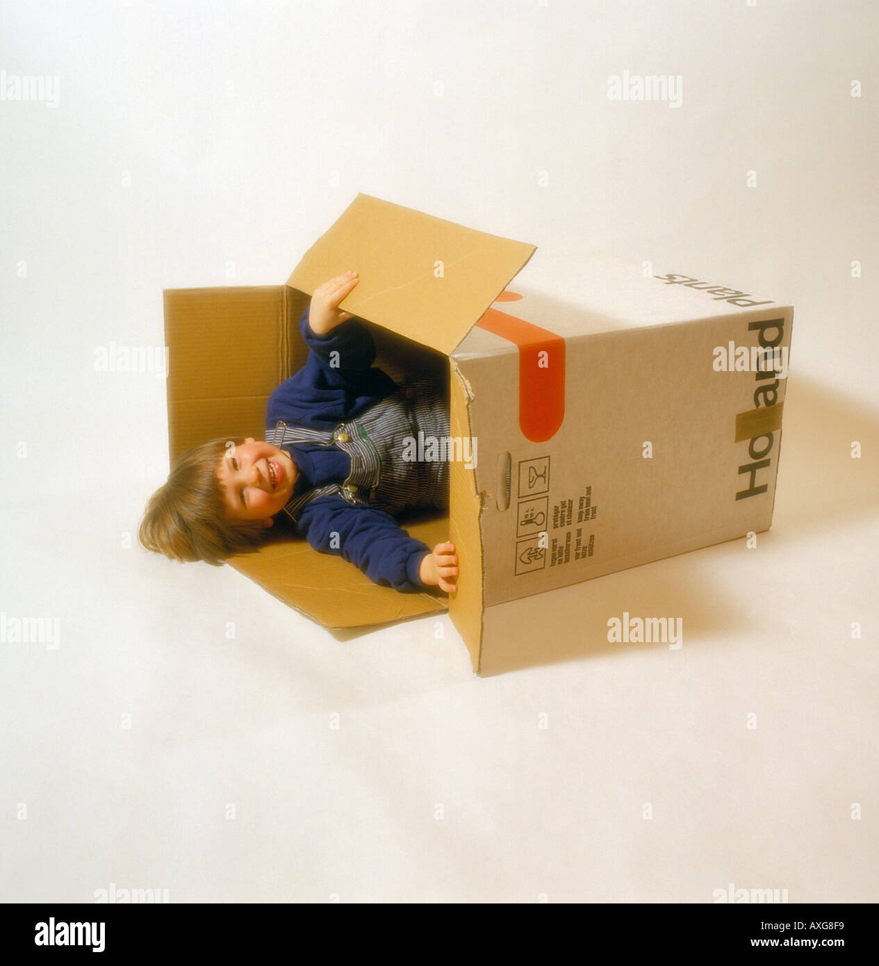 child playing and hiding in a  cardboard box. Photo by Willy Matheisl - Stock Image