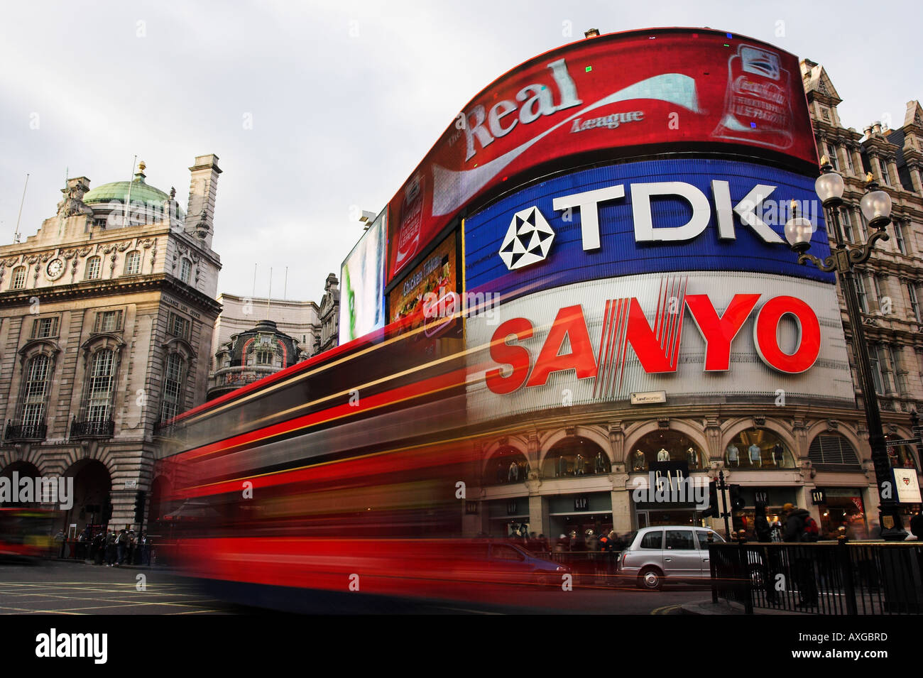 Picadilly Circus, London with bright billboards and red double decker bus blurred in foreground. Stock Photo