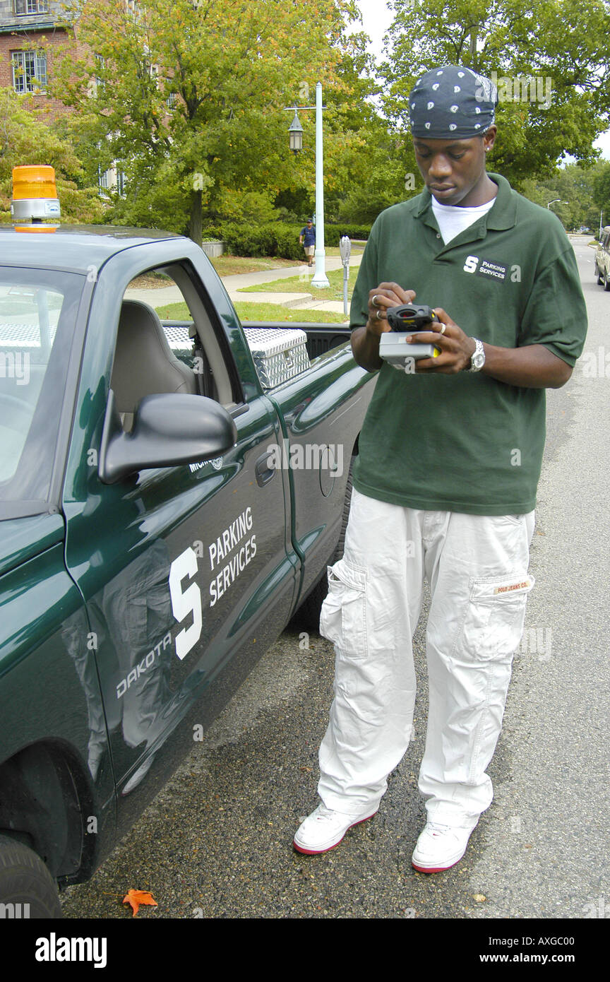 Black Michigan State University student works part time with campus parking enforcement services - Stock Image
