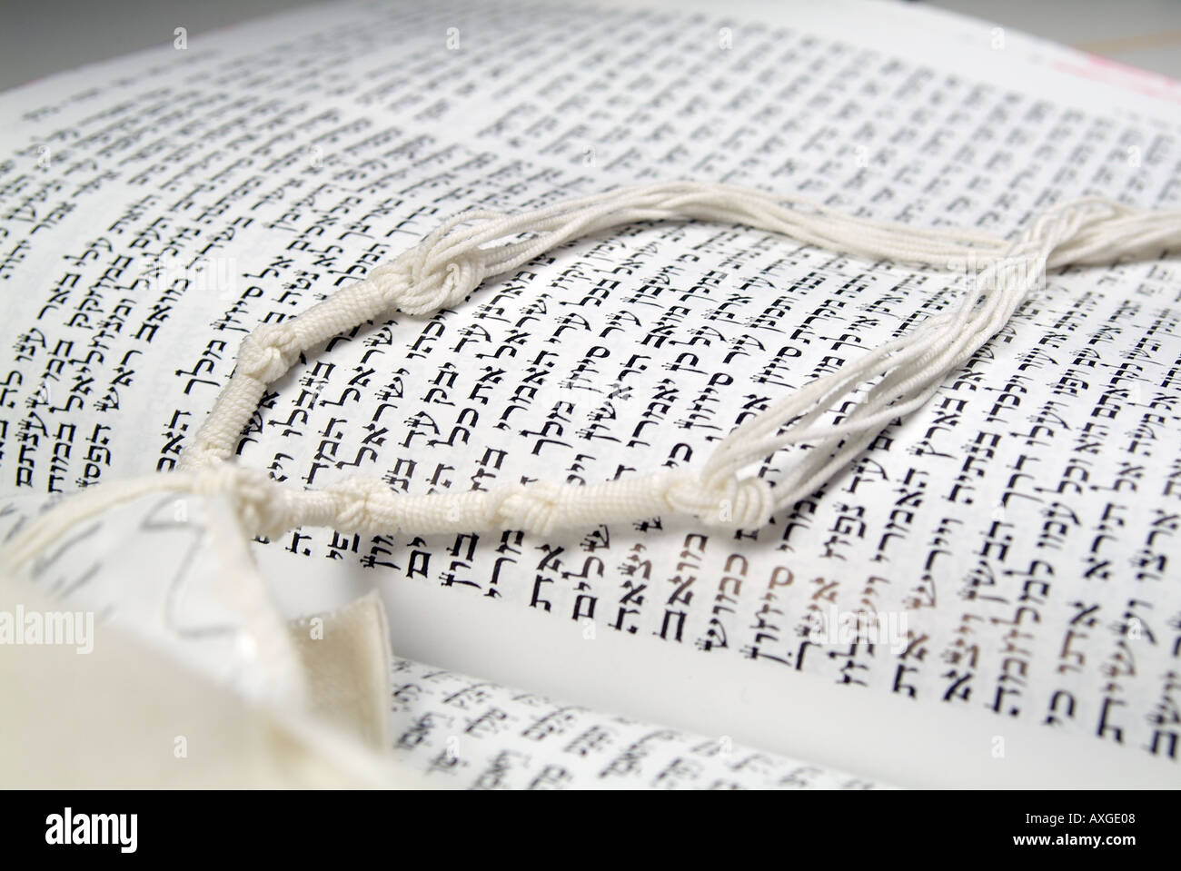 Hebrew text in holy book with tallit pray shawl fringes - Stock Image