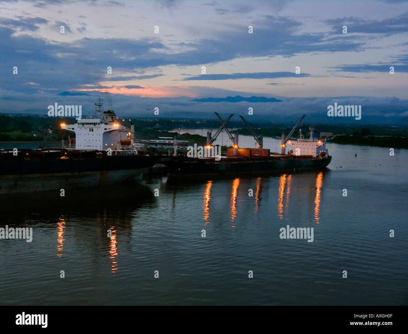 Bulkcarriers in the port during sunset. - Stock Image