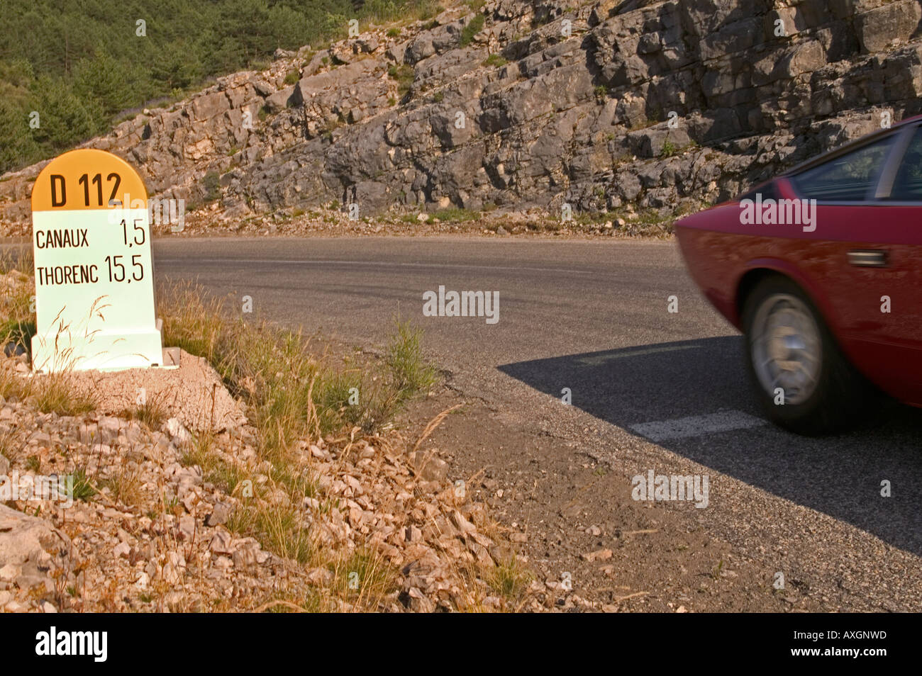 Classic car passing kilometer post in French alps - Stock Image