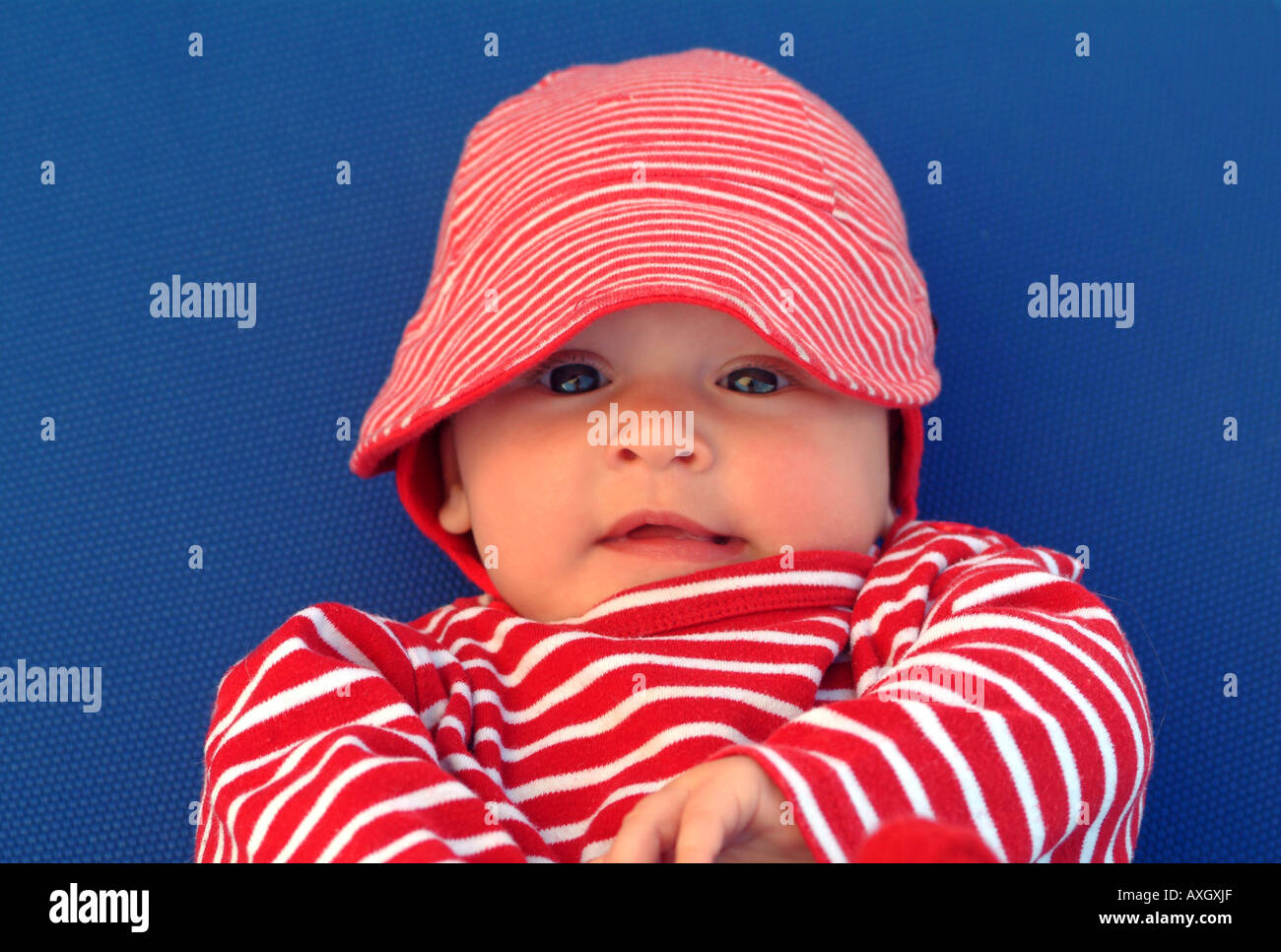 confident 6 months old Baby with hat closeup zufriedenes 6 Monate altes Baby mit Mütze - Stock Image