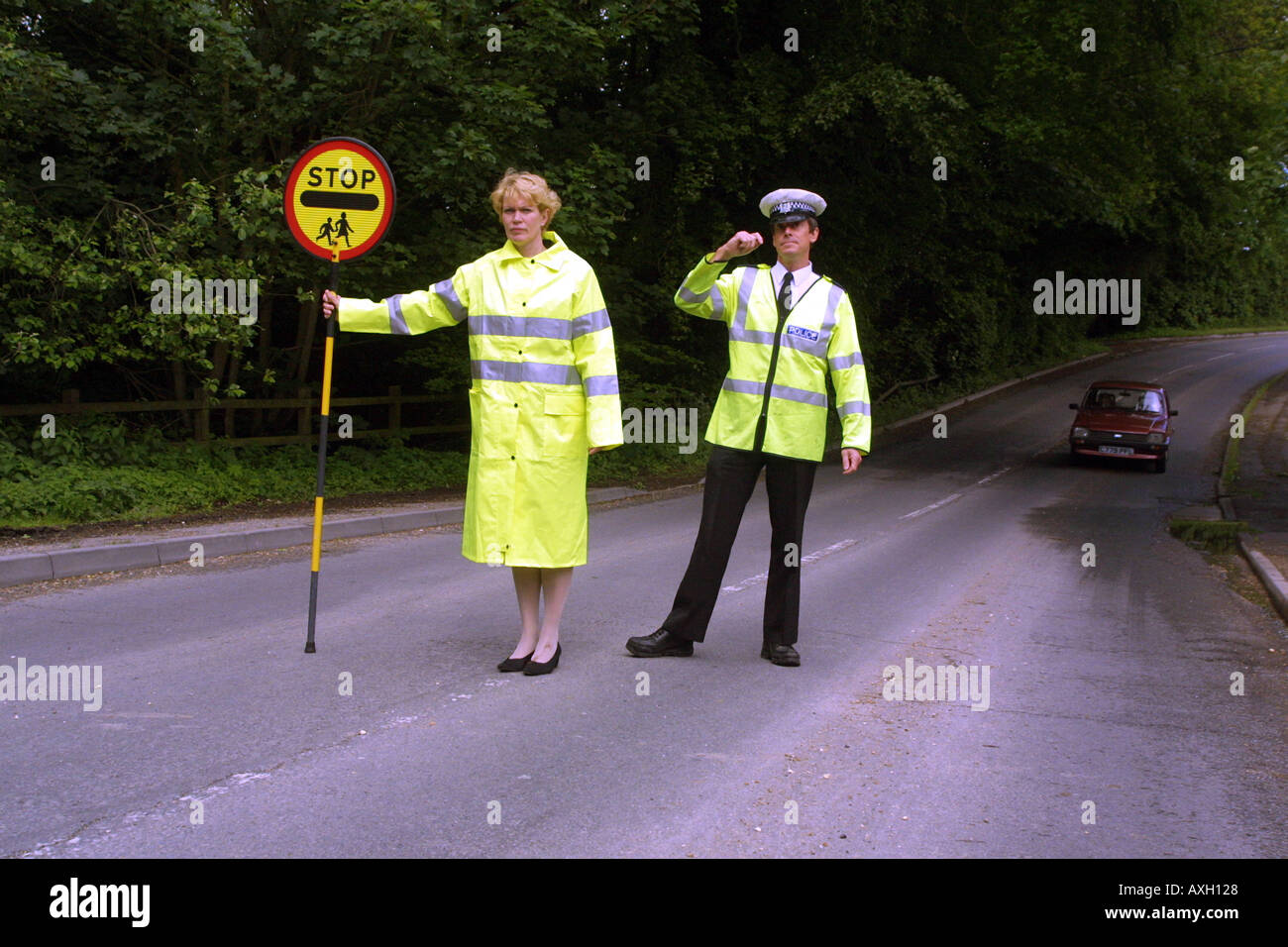 School crossing patrol woman with stop sign and police officer on the road. England UK European - Stock Image