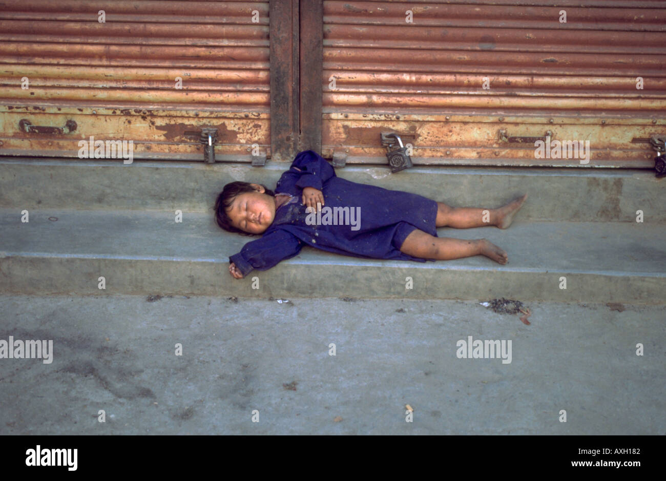 Homeless Child sleeping in the streets of Kathmandhu Nepal - Stock Image