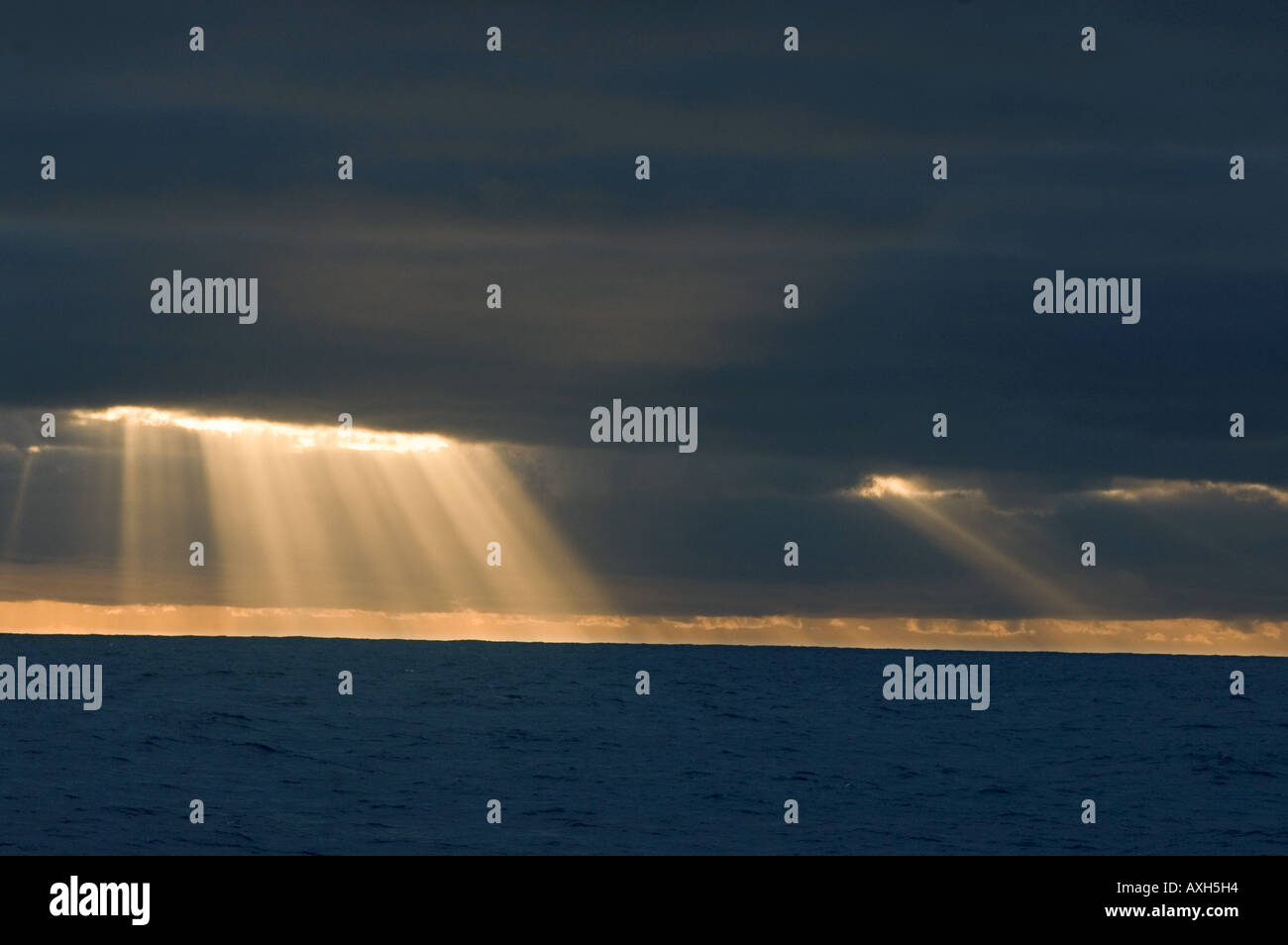 Sun rays between clouds in south Pacific Ocean. - Stock Image