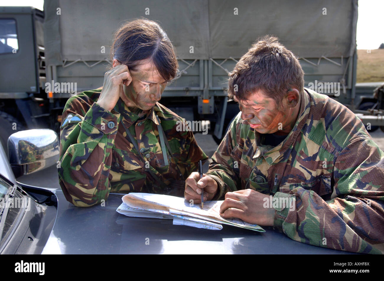 A BRITISH ARMY FEMALE RECRUIT CHECKS A MAP WHILE BEING BRIEFED BY A COLOUR SERGEANT BEFORE A TRAINING STALK DURING - Stock Image