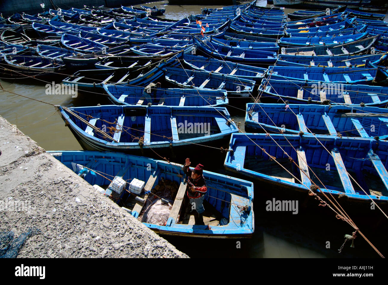 Man tying a boat in port Essaouria Morocco - Stock Image