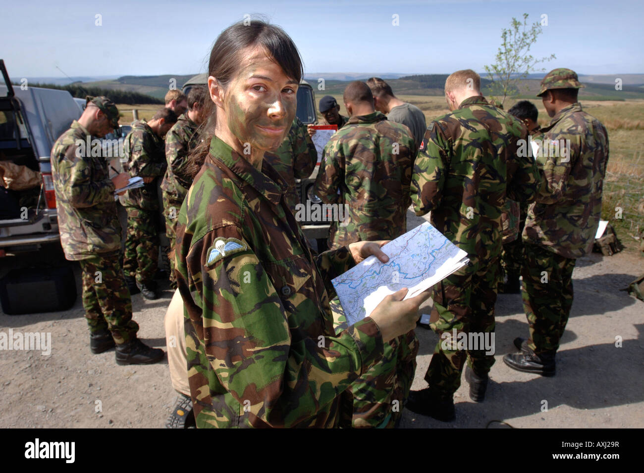 A BRITISH ARMY FEMALE RECRUIT CHECKS A MAP BEFORE A TRAINING STALK DURING A SNIPER COURSE IN BRECON WALES - Stock Image