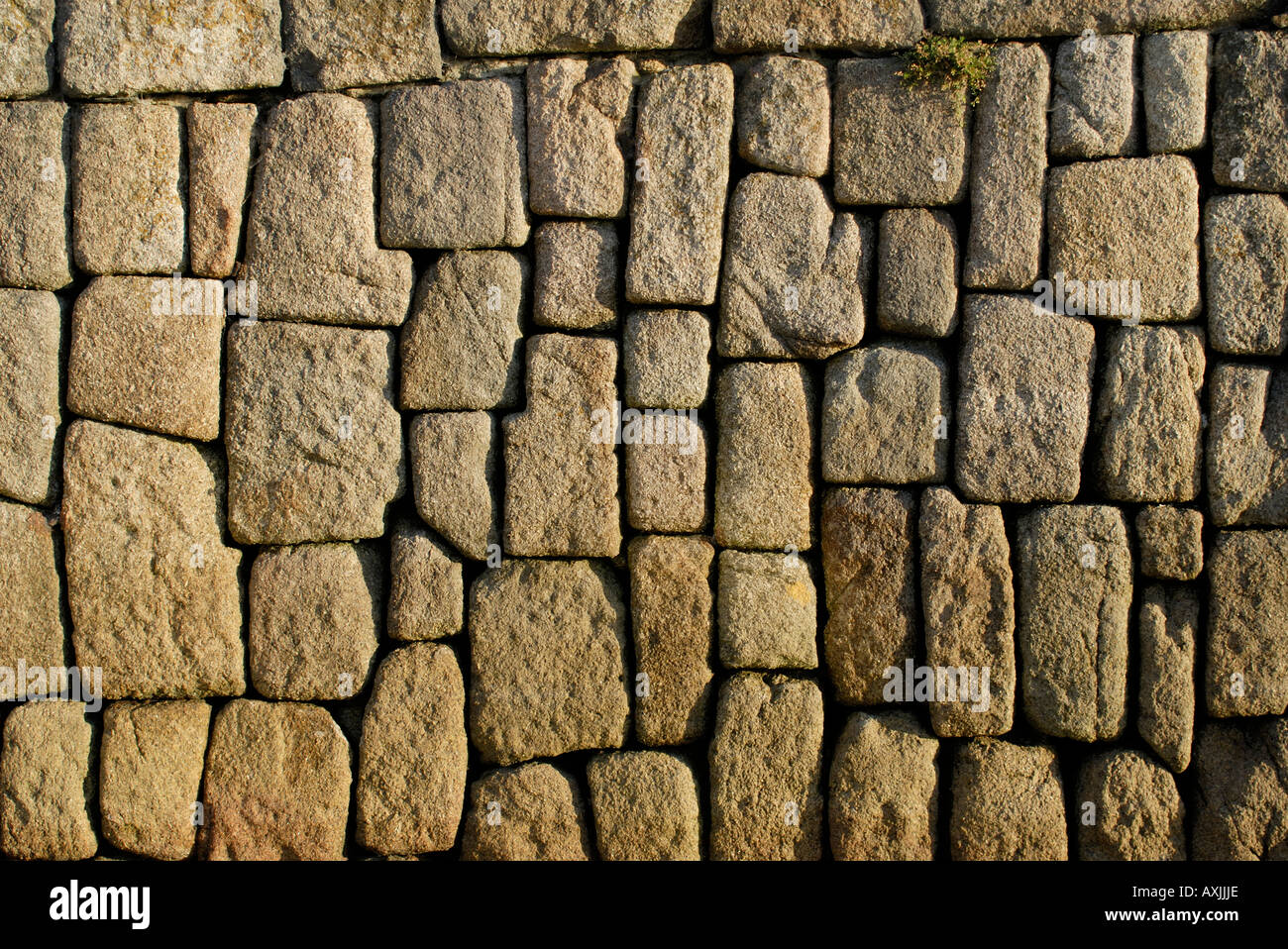 The harbour walls at Hugh Town are built from blocks of granite - Stock Image