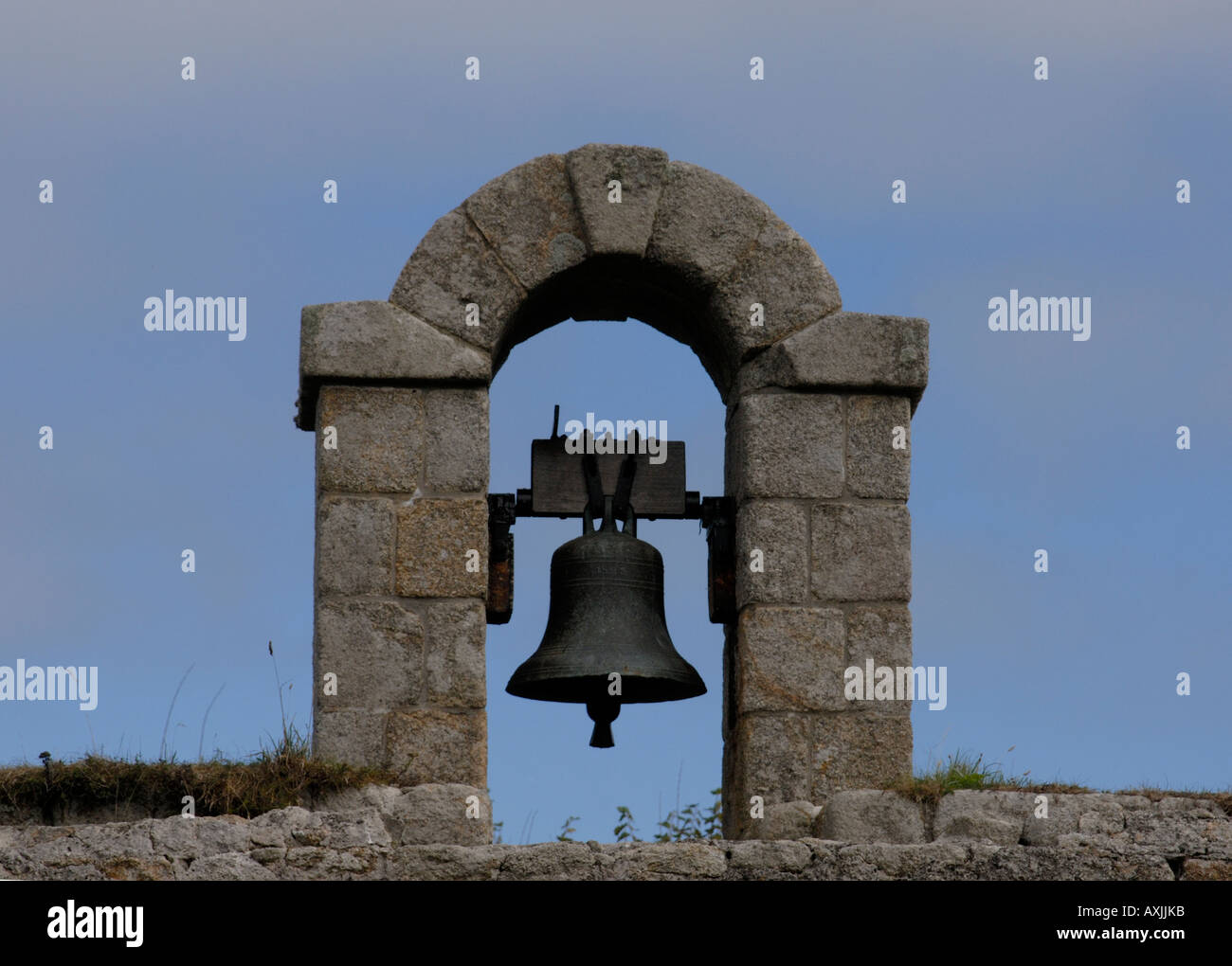 Bell set in the lichen covered granite walls of the Garrison above Hugh Town St Mary  Isles of Scilly UK - Stock Image