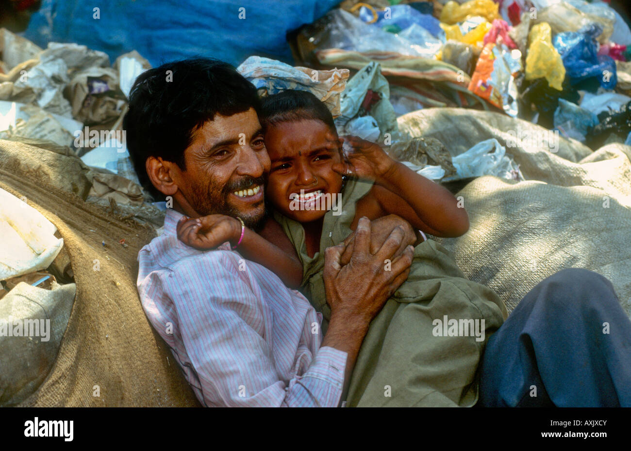 Father holding crying daughter in the middle of rubbish dump where they live homeless on the outskirts of Mumbai - Stock Image