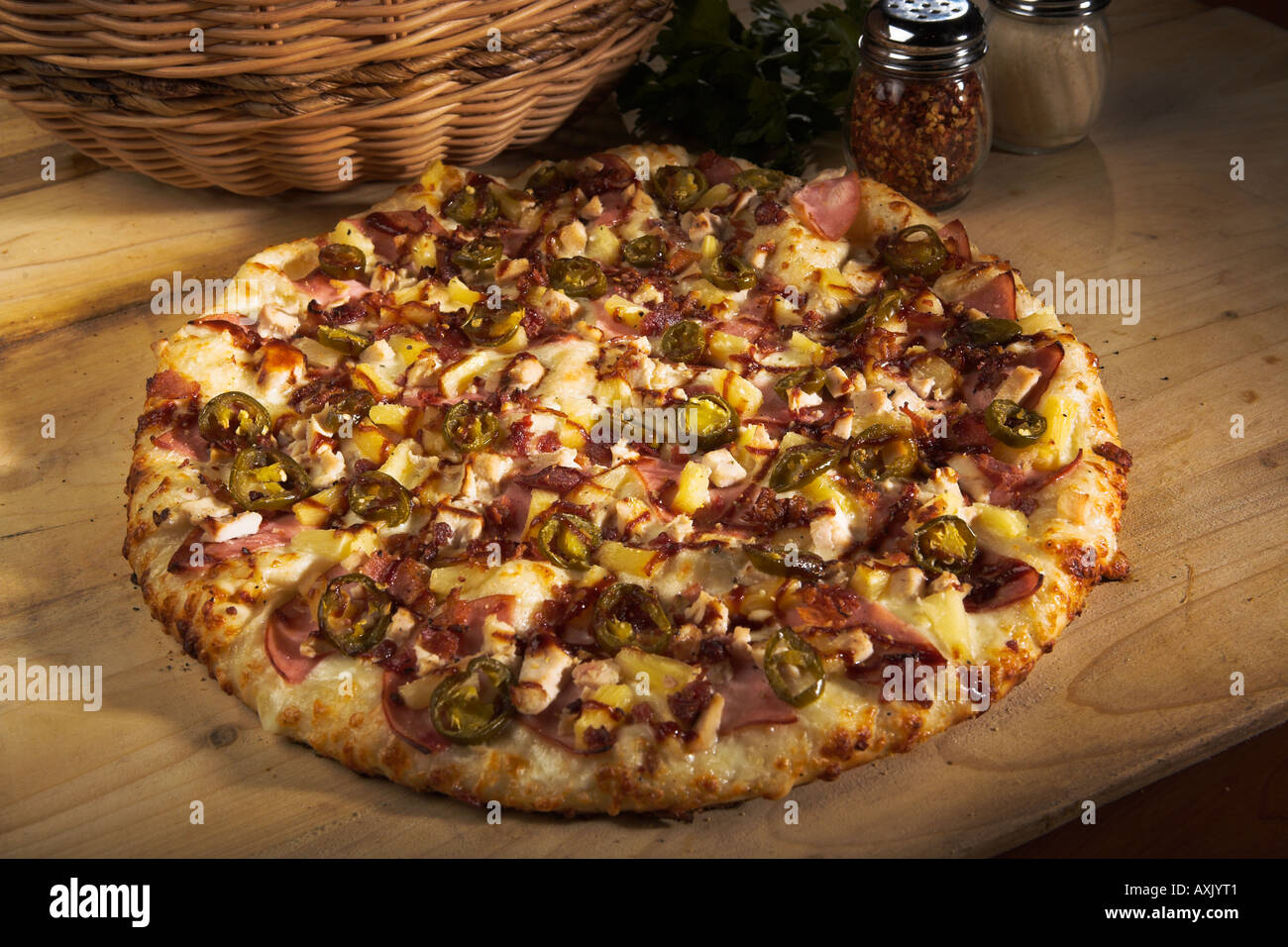 baked pepper vegetable meat pizza with cheese sauce bred crust brown on wood cutting board next to basket tomatoes - Stock Image