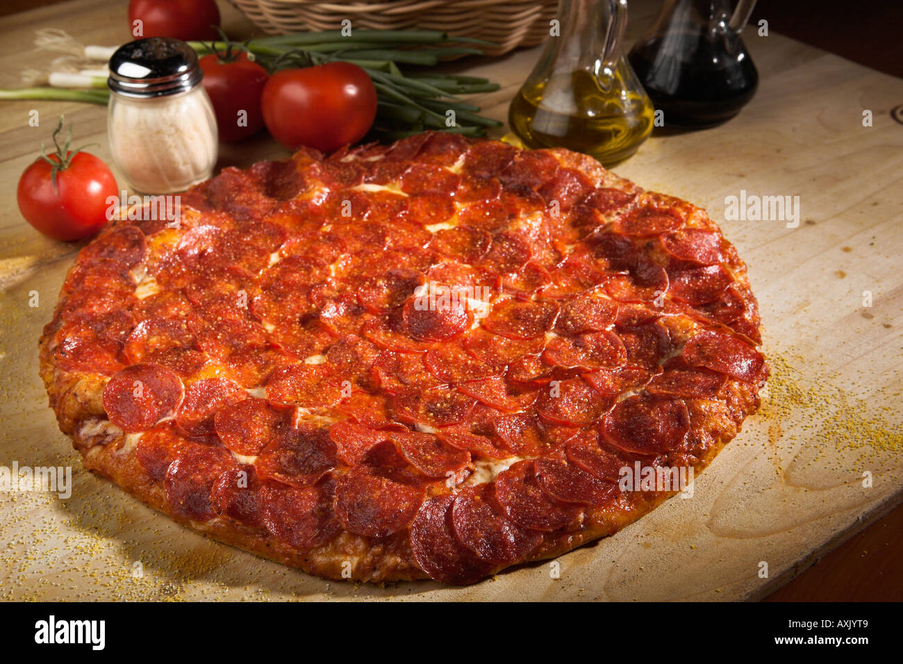baked pepperoni meat pizza with cheese sauce bred crust brown on wood cutting board next to oil basket tomatoes - Stock Image