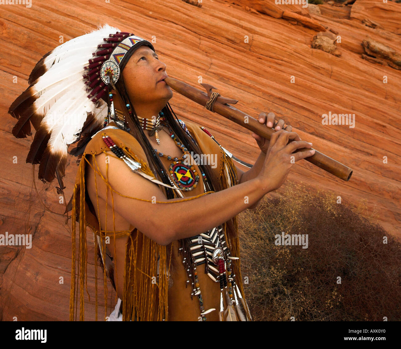 Native American Indian man person with cultural outfit uniform headdress feathers playing music instrument horn whistle - Stock Image