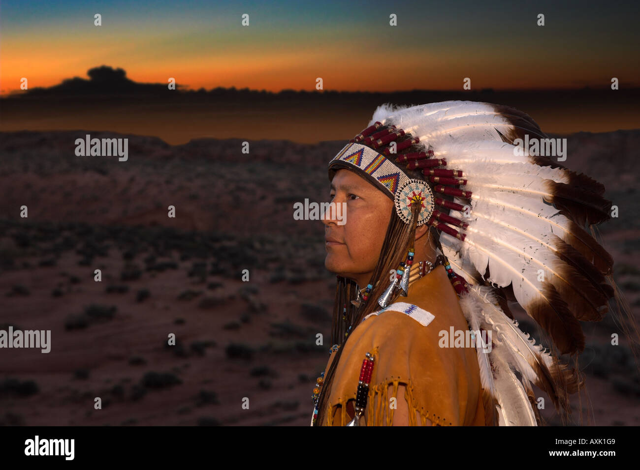 Native American Indian man with cultural outfit uniform headdress feathers design patterns leather band nature sunset sunrise - Stock Image