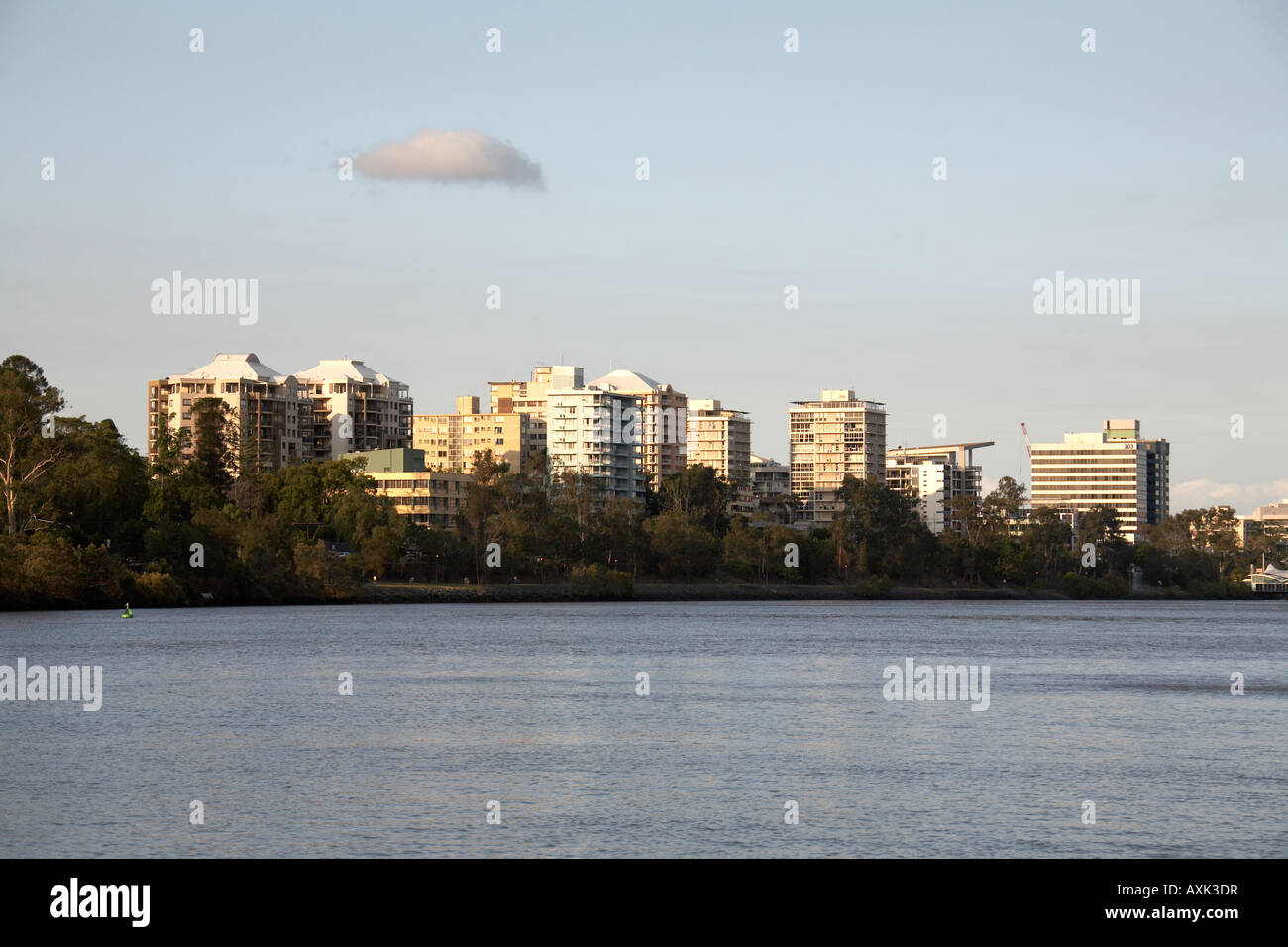 Residential buildings beyond the river in evening light Brisbane Queensland QLD Australia - Stock Image