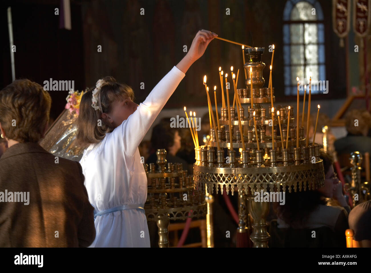 Young girl lighting candles before Easter Good Friday