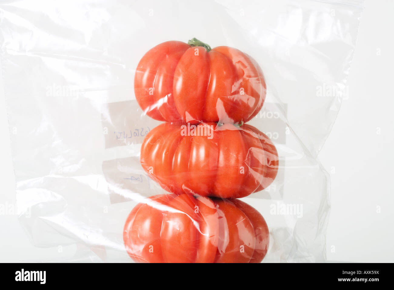 Heirloom tomatoes stacked in plastic bag, close-up - Stock Image