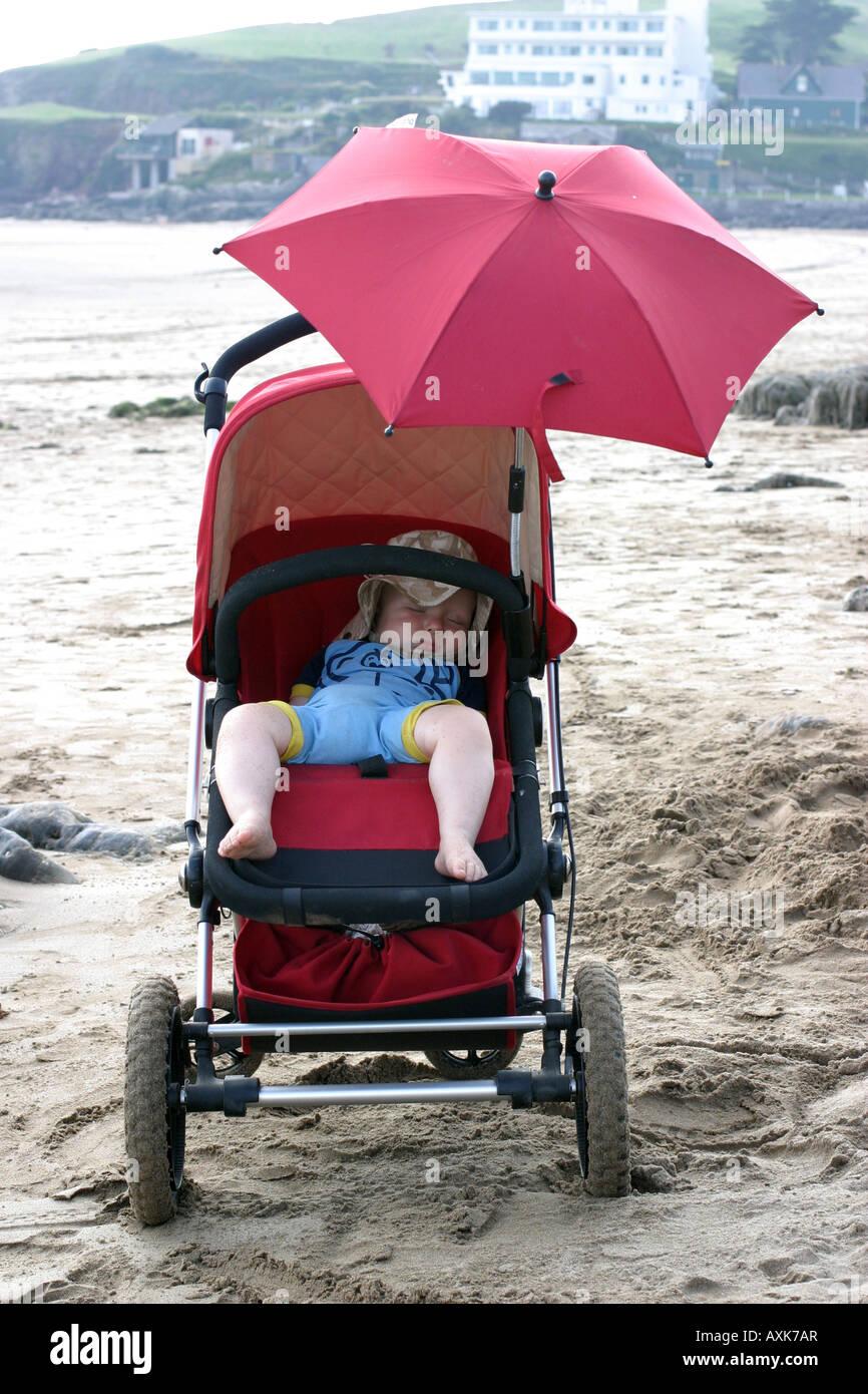 Baby sleeping on beach - Stock Image