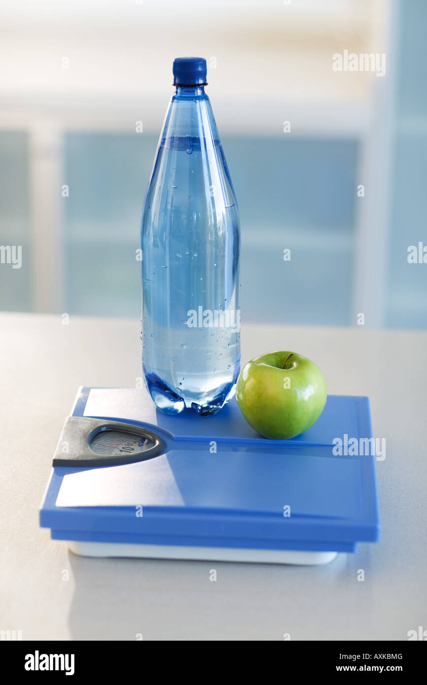 Green apple and water bottle on bathroom scale, close-up - Stock Image