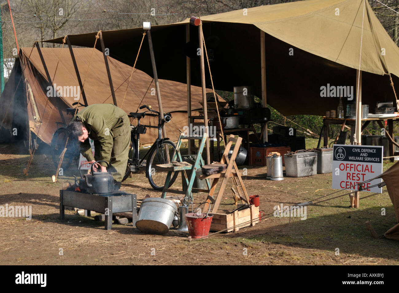 person in uniform cooking over stove  weekend Peak District Derbyshire England UK - Stock Image