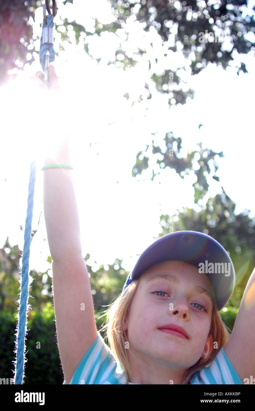Photograph of young girl posing in the sunshine with baseball hat on family summer holiday UK. - Stock Image