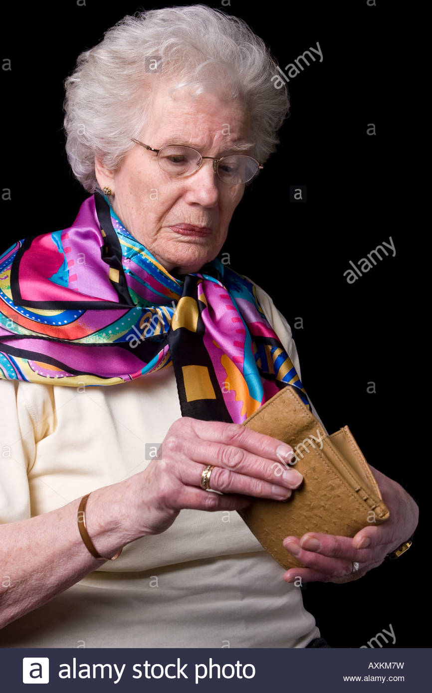 An old woman holding her purse and looking worried. - Stock Image