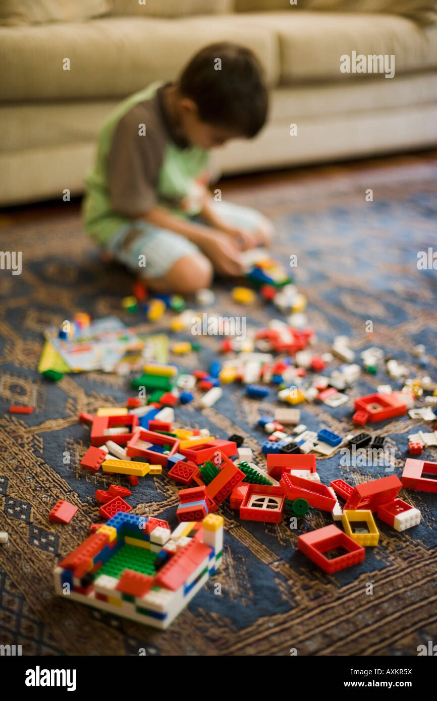 Boy aged six years plays with Lego building blocks Stock Photo