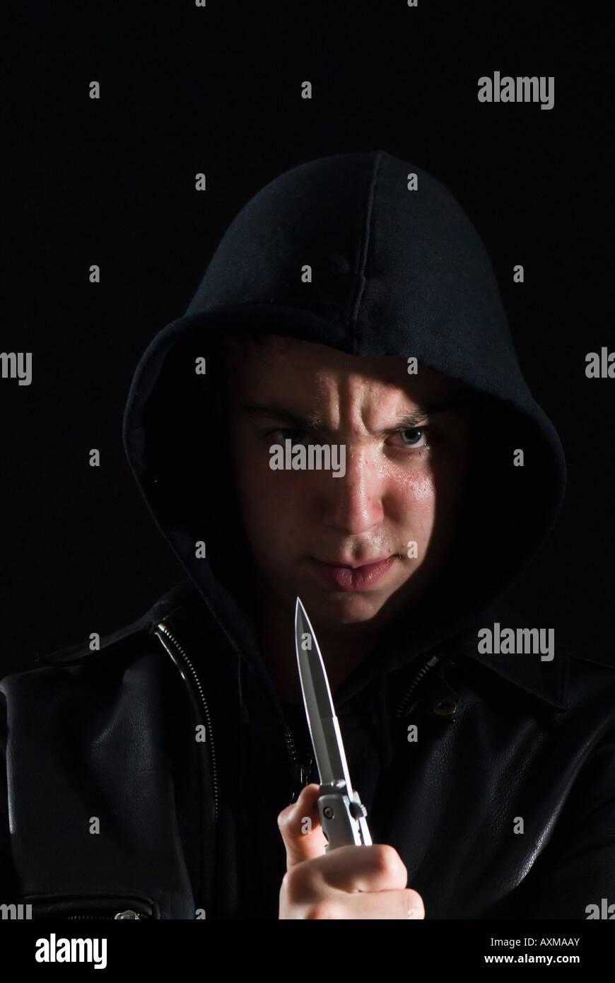Teenage thug in hoody with knife - Stock Image