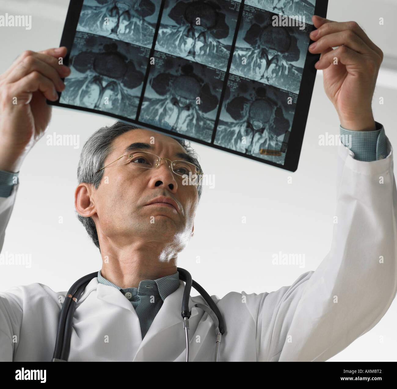 Male doctor looking at x rays - Stock Image