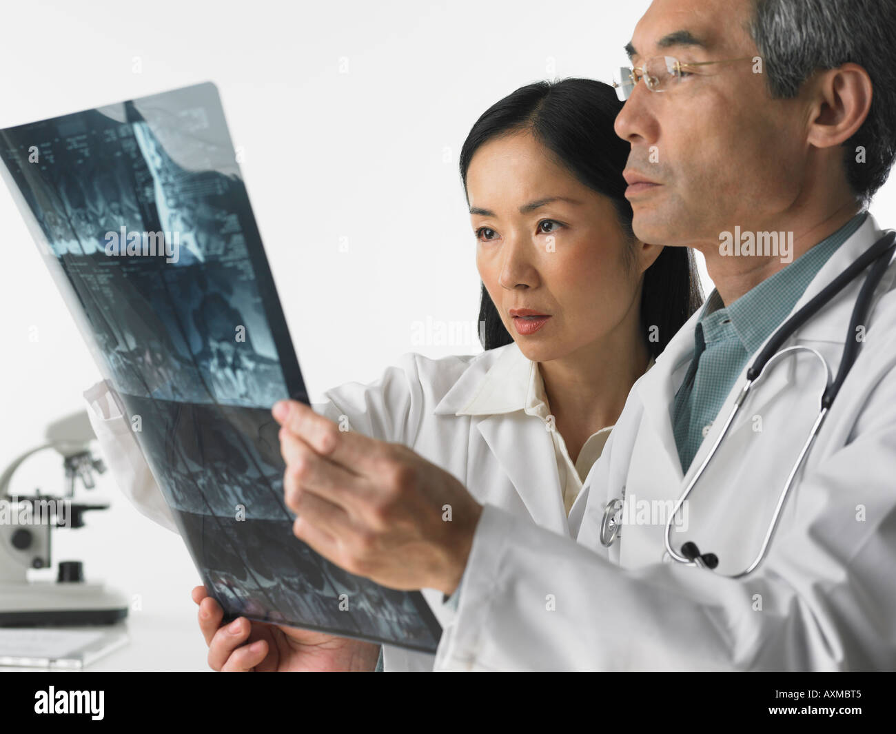 Male and female doctors looking at x rays - Stock Image