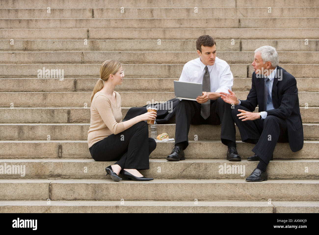 Three business people talking outdoors on stairs with laptop - Stock Image