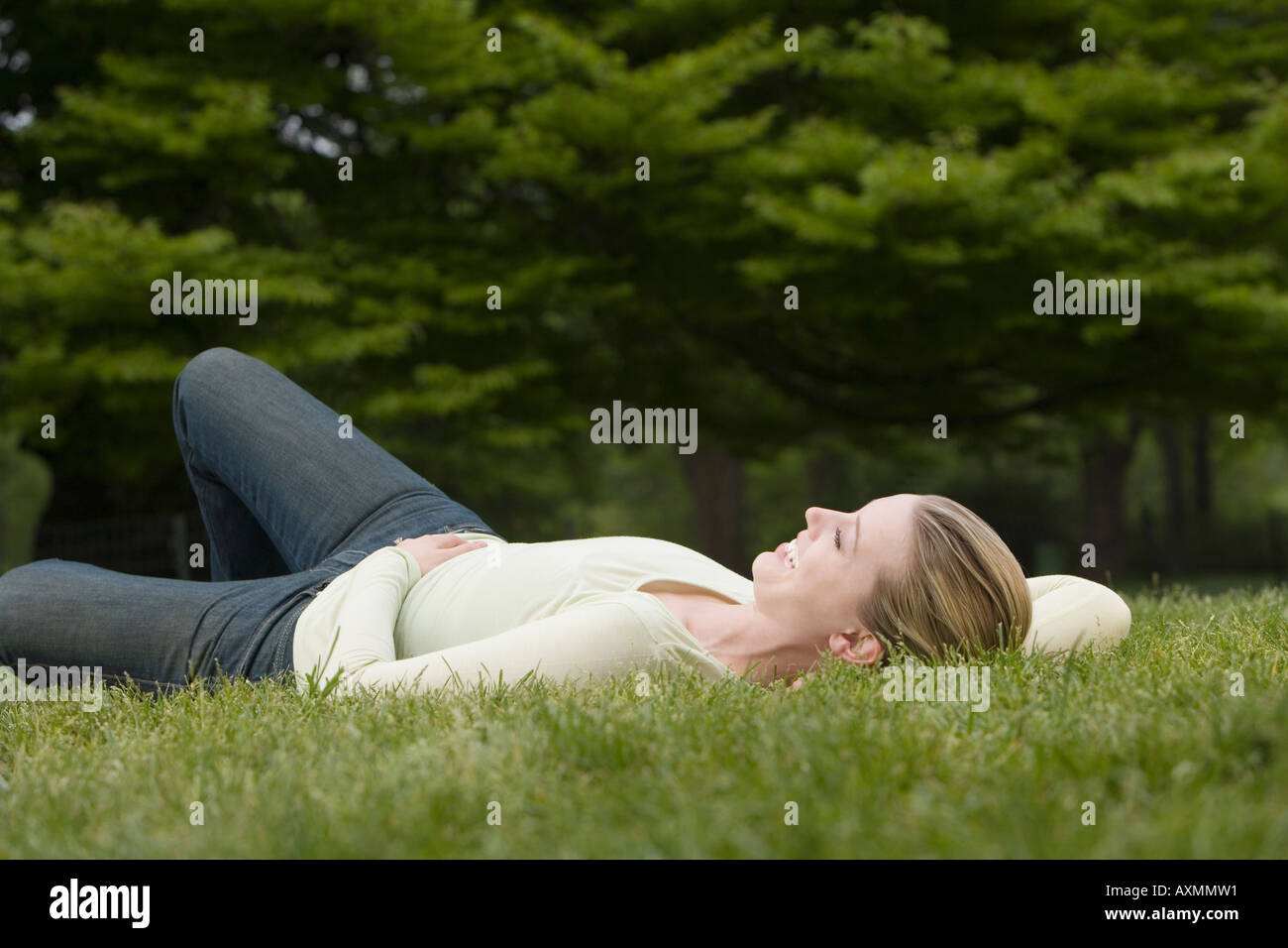 Pretty young woman lying on grass - Stock Image