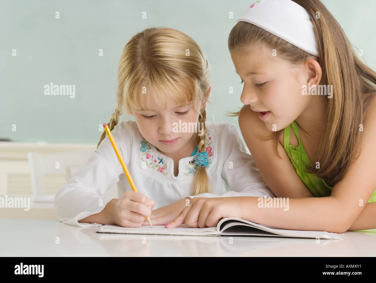 Girl helping classmate at desk - Stock Image