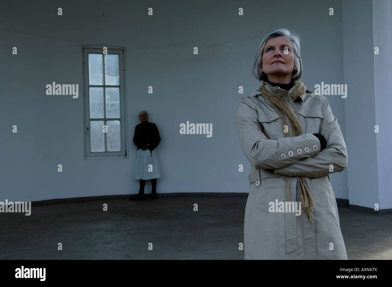 Two mature women standing in an empty room - Stock Image