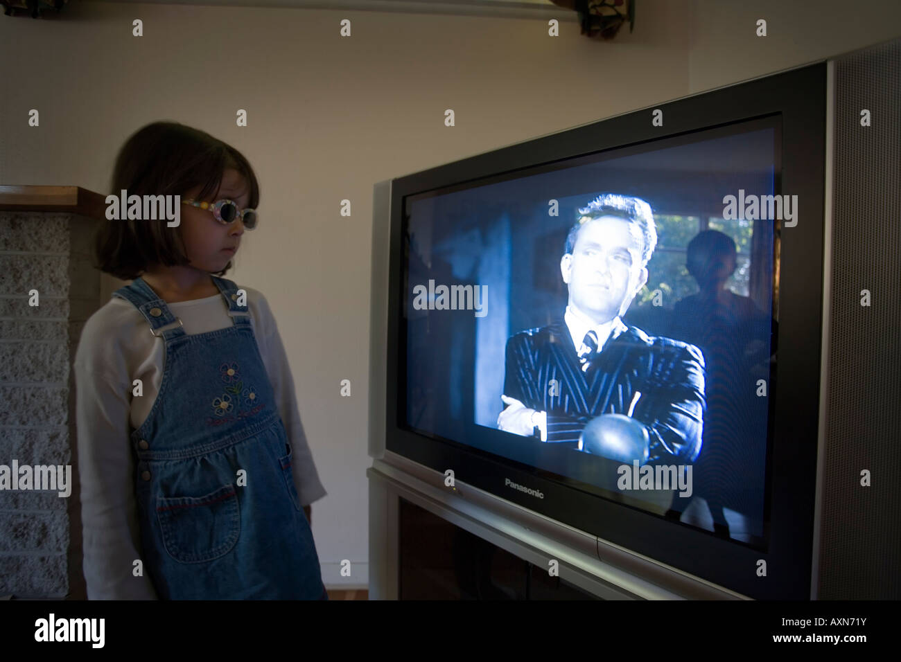 Girl aged four with sunglasses watches TV with man on programme and brother reflected in screen behind her - Stock Image