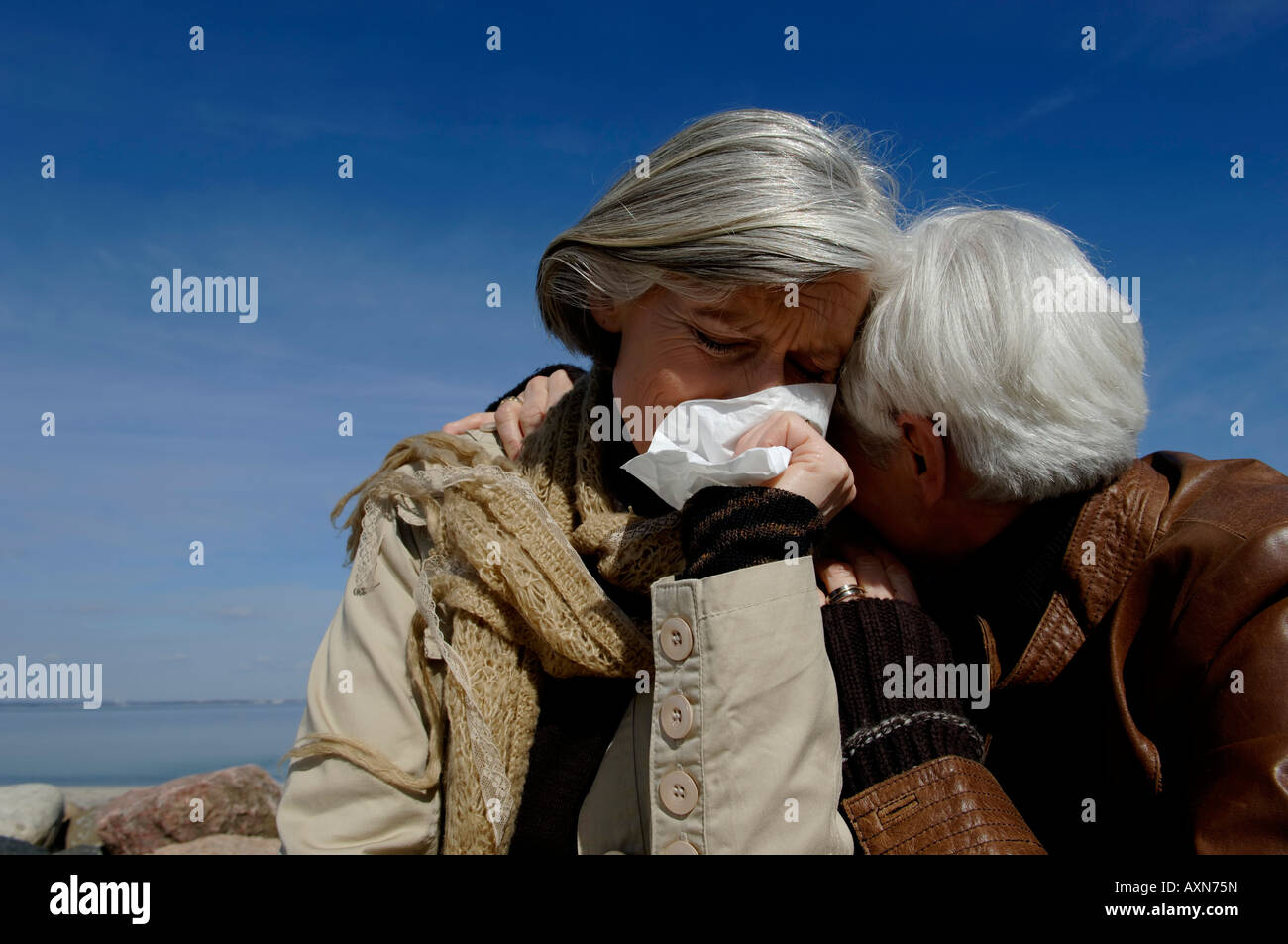 Two mature women embracing each other, one woman crying - Stock Image