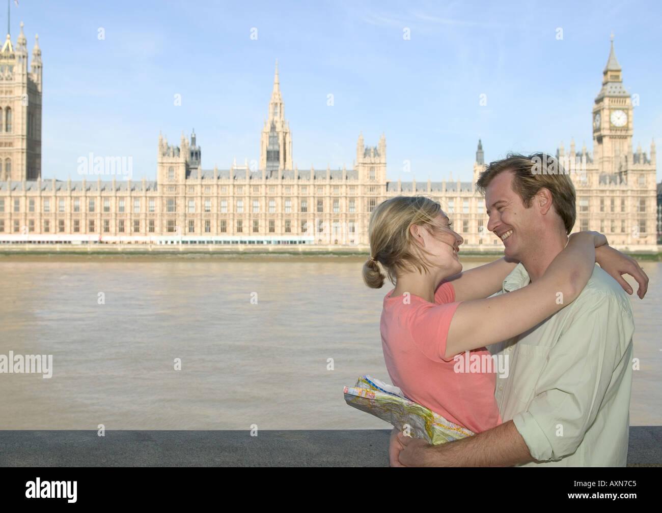 young couple embracing on short break in london opposite big ben - Stock Image