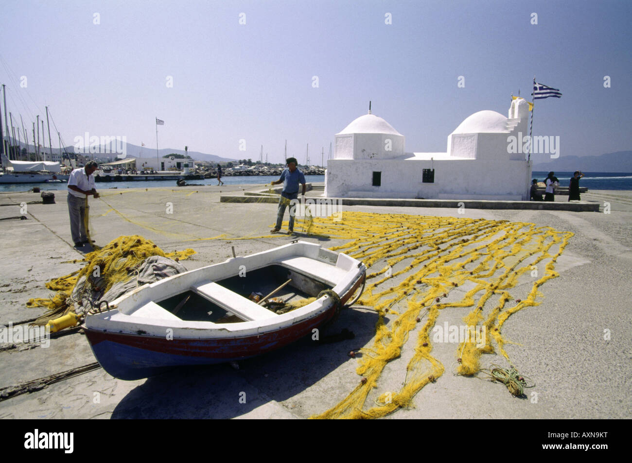 Argo Saronic Islands Small white washed church Flag Harbour Men with fishing nets Boat on land - Stock Image