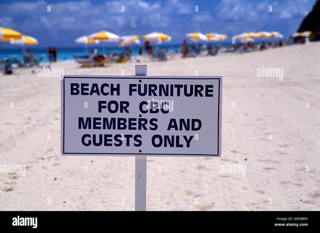 Private beach club sign with yellow and white umbrellas , Bermuda Stock Photo