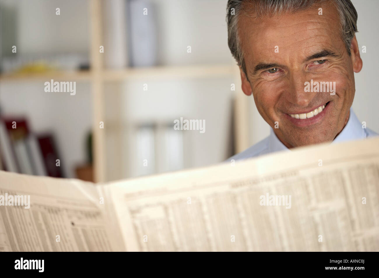 Smiling senior businessman reading a newspaper - Stock Image