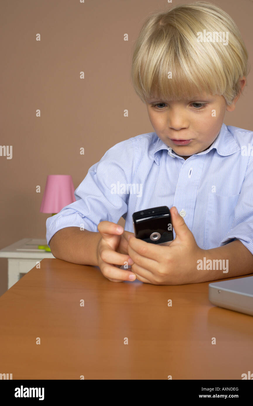 Boy (4-5 Years) holding a mobile phone - Stock Image