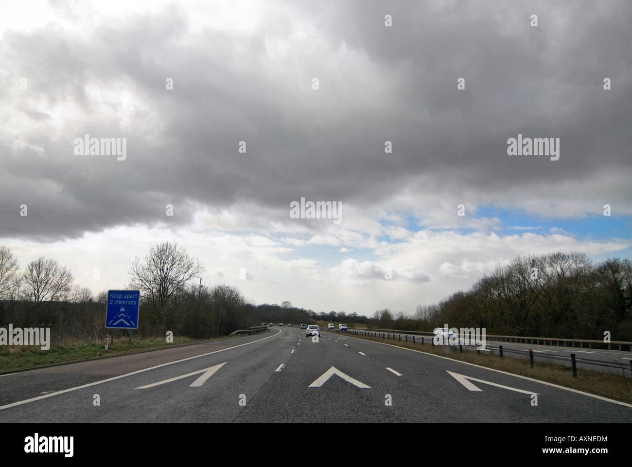 """Horizontal wide angle of the """"two Chevron apart"""" sign and road markings on the motorway on a sunny day Stock Photo"""
