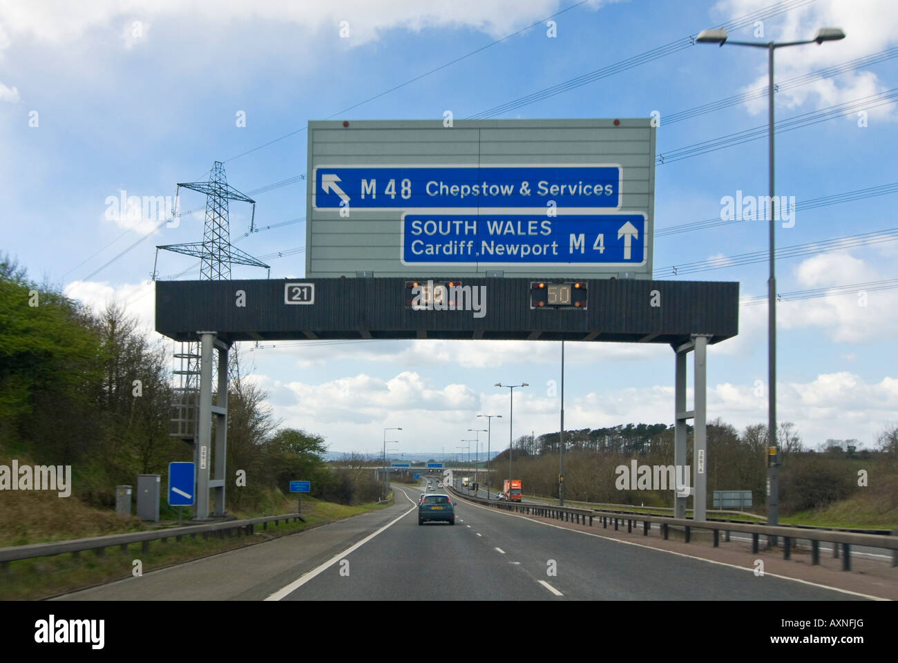 Horizontal view of cars driving underneath a motorway gantry sign with the matrix lights flashing to slow down. Stock Photo