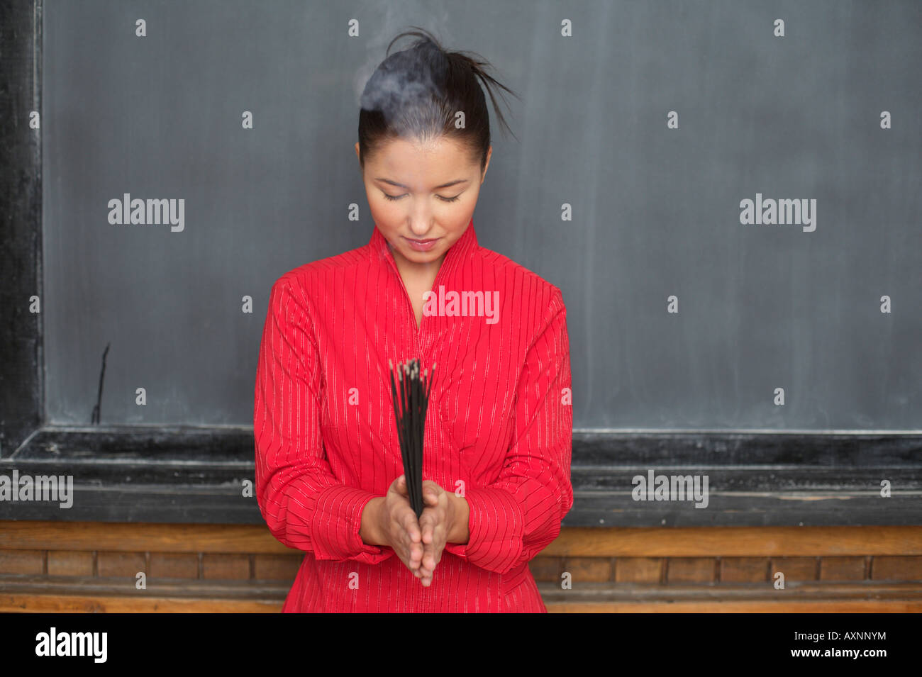 Asian woman is holding chopsticks in front of a blackboard - Stock Image