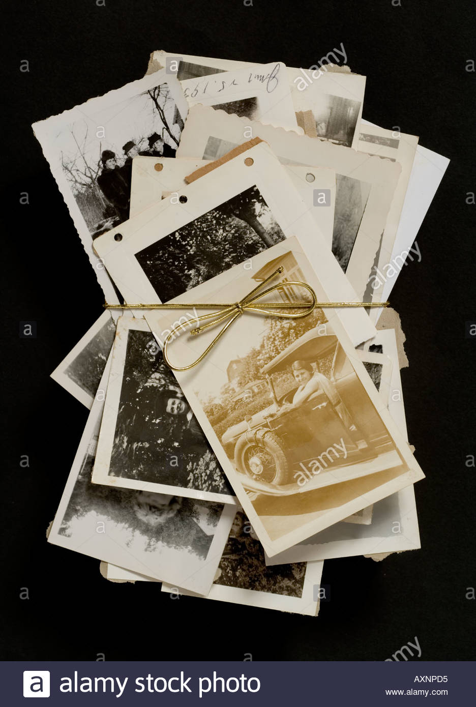 various old photographs hold together with a golden bow tie string - Stock Image