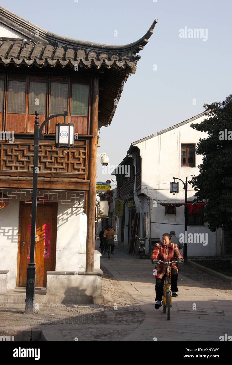 Chinese woman cycling in the 'old town' of Suzhou,China - Stock Image