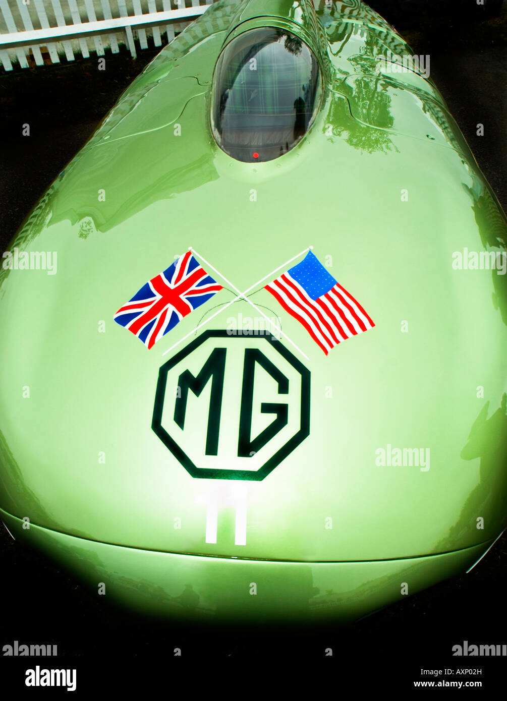 Curvy green MG historic racing car with crossed Union Jack British and USA stars and stripes flag painting logo - Stock Image